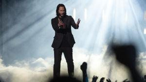 En man står med händerna utsträckta rakt framför sig på en scen. Bakom honom ses rök ur en rökmaskin.
