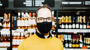 En man klädd i gul tröja står framför en butikshylla med drycker på i Alko. Han har munskydd på sig och tittar in i kameran.