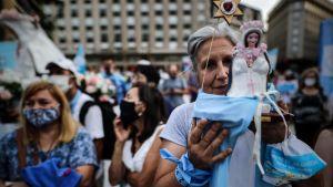 En kvinna som demonstrerar i de argentinska abortmotståndarnas ljusblå färger håller upp en liten staty av junfru Maria.