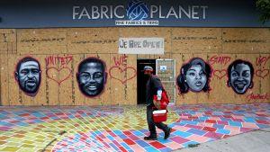 Väggmålning av fyra människor. Framför väggen går en man.
