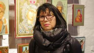 En mörkhårig kvinna i dunjacka och stora glasögon står framför en vägg med ikoner.