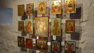 Flera ikoner hänger i ett mönster på en vägg.