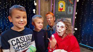 Programledaren för Superhjälparna har grädde i ansiktet och bredvid henne står två pojkar och karaktären Klasu och ser glada ut medan