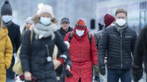 Människor i munskydd går i ett vinterklätt Helsingfors.