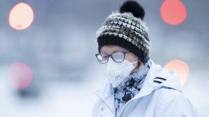En person i munskydd går ute i vintervädret. Hon har immiga glasögon på sig och mössa.