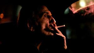 Harry Dean Stanton lähikuvassa profiilissa tupakka suussa. Kuva dokumenttielokuvasta.