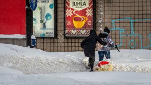 Två kvinnor klättrar över en snövall vid övergångsstället