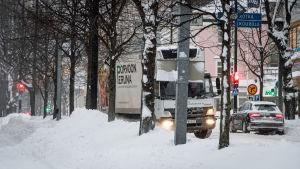 Bilar kör längs väldigt snöig gata