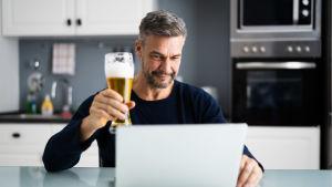 Man sitter i ett kök och skålar med en öl mot en datorskärm.