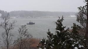 En patrullbåt från Sjöbevakningen kör i ett sund en dimmig vinterdag.
