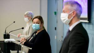 Tre personer står vid mikrofoner klädda i munskydd. I förgrunden en man, bakom honom två kvinnor.