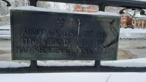 En skylt med texten: Aurorasäöllskapet 1771-1779 verkade i en byggnad belägen på denna plats. Bakom skylten syns en snöig och isig åstrand.