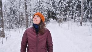 En kvinna som står på en väg och tittar upp mot träden.