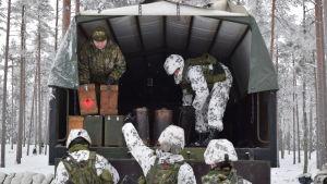 Rekryter packar stormlyktor ur en lastbil inför en övernattning i Galoppskogen utanför Ekenäs.