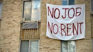 """Ett lakan med texten """"Inget jobb, ingen hyra"""" hänger ner för en husvägg."""