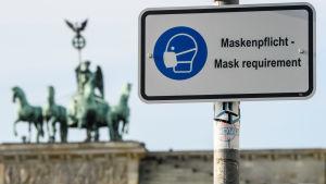 På en vit skylt står det att munskydd krävs - en bild av en person klädd i munskydd finns på skylten i blått. I bakgrunden syns ett monument där fyra hästar drar en vagn med en person i.