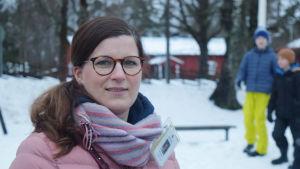 Rektor Jessika Elfving på skolgården utanför Kyrkfjärdens skola. Elever i  bakgrunden.
