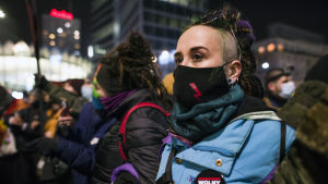 En kvinna i svart munskydd med en röd blixt på.