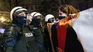En kvinna håller upp ett plakat framför poliser i Polen.