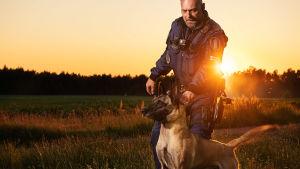 En polis med en schäferhund i solnedgången.