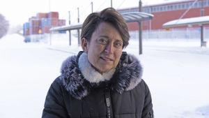 En kvinna ser in i kameran vid en parkeringsplats