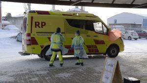 Ambulans och personal vid en covid provtagning