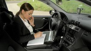 Nainen istuu auton etupenkillä kuljettajan paikalla kannettava tietokone sylissään, puhelin korvallaan ja kirjoittaa samalla paperiseen kalenteriin.