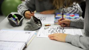 Två elever sitter vid en bord och gör läxor.