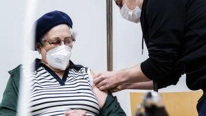 En äldre kvinna får en spruta i armen.