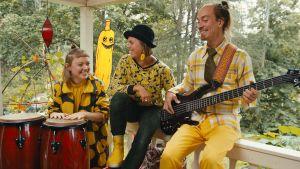 Tre musiker sitter bredvid varandra och ler