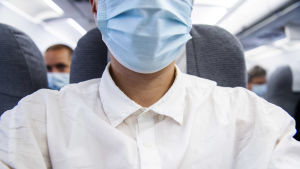 Manlig flygpassagerare i vit skjorta och ljusblått munskydd ombord på ett passagerarplan.