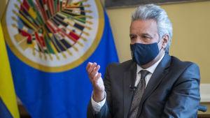 Bild på man i kostym. Han sitter med en hand upplyft och bär munskydd. I bakgrunden skymtar Ecuadors flagga.