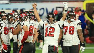 Tom Brady omgiven av glada amerikansk fotboll-spelare under NFL-finalen 7.2.2021.