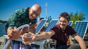 Lauri Reuter ja Henri Alén kaatavat tislattua vettä juomalasiin.