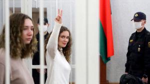 Två kvinnor och en polis. Ena kvinnan håller upp fredstecknet med fingrarna.