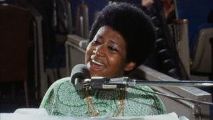 Aretha Franklin laulaa kirkossa pianon takana. Kuva dokumentista Amazing Grace (1972).