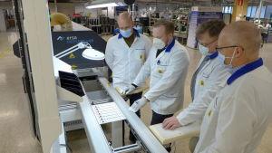 Flera personer granskar blåstester på en fabrik.