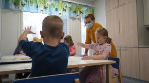 Päiväkotilapset leipomassa opettajan seurassa.