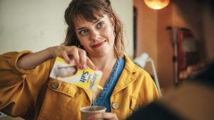Oona (Anna Airola) kaataa hymyillen suolaa pahviseen kahvikuppiin.