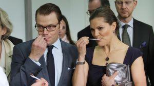 Kruununprinsessa Victoria and Prinssi Daniel syövät lusikoilla jotain juhlissa.