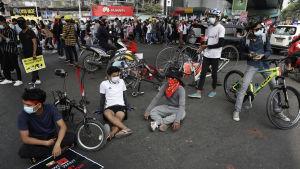 Unga personer samlas på gata och sitter med skyltar.