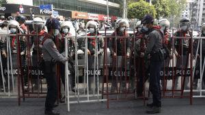 Kravallpolis står och vaktar under en protest i Myanmar.