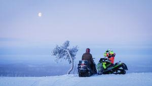 Kaksi moottorikelkkailijaa vaaran laella talvisessa Lapissa