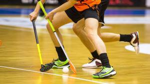 Fötterna på två innebandyspelare i närkamp om bollen
