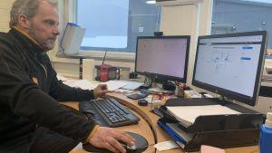 En man sitter vid en dator med två skärmar.
