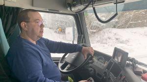 En man sitter i hytten på en  lastbil