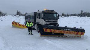 En man med arbetskläder står intill en stor plogbil i snön