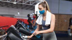 En kvinna i munskydd torkar av en löpmatta med en handduk på gymmet.