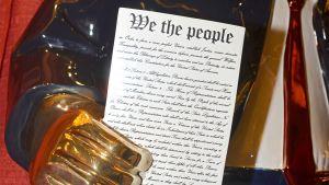 Närbild på konstitutionen Trumpstatyn i guld håller i.