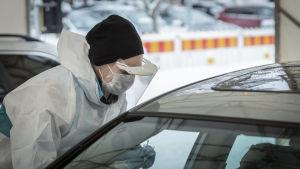 En person i skyddsutrustning tar ett coronatest av en person som sitter i bil.